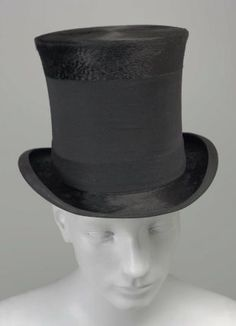 Late 19th Century Hat  Men's black, high silk hat with wide black wool band and narrower black broadcloth band at base of crown; edge of brim bound with black silk; printed label in lining: Cooksey and Co., 57 Cheapside, London.