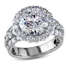 This luxurious diamond ring features a four-carat round-cut white diamond center…