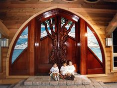 """""""The Triplets"""" by Fine Woodworks Custom Doors. This Gothic style entry features carvings of the family's children and stained glass windows. Made of Hand-Carved Honduran Mahogany and Stained Glass. Visit our website for additional photos and pricing. Woodworking Jointer, Woodworking Logo, Fine Woodworking, Woodworking Classes, Stained Glass Door, Custom Stained Glass, Wooden Double Doors, Wooden Doors, Front Door Entrance"""