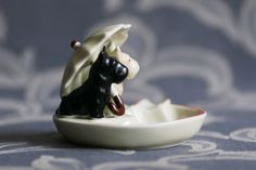 SCOTTIE DOGS ASHTRAY ILMENAU   Tiny vintage ashtray with pair of scottie terrier dogs, hand painted porcelain was made about the year 1960 in Thuringian porcelain factory in Ilmenau. Marked on the bottom with brown mark V.E.B. Zier- u. Werbeporzellan Ilmenau used in the years 1952-1974 and by incised model No. 6696.   Dimensions: 7x8x9 cm  Weight: 150 g