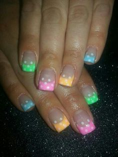 Nude nails with Brightly colored tips in various different summer colors with white polka dots done with a band aid and the white applied with a sponge, free hand nail art