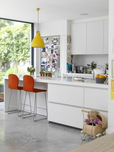 """Unlike in previous homes, Irenie bought rather than designed the fitted kitchen, choosing units from Bulthaup. """"I got to be the client for a change!"""" she laughs. Contrasting with the white units and poured concrete floor, colour is introduced through the orange Jasper Morrison chairs and vintage pendant light."""