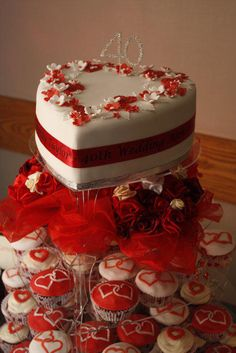 This was made for my parents' Ruby Wedding Anniversary. The main cake was a rich fruit cake made several months in advance and fed regularly with brandy. The week before the party it was covered in marzipan and then white fondant and decorated...
