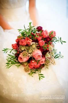 Scabiosa pods, roses and fresh red berries come together for a beautiful rustic wedding bouquet.