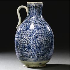 A LARGE AND RARE KÜTAHYA BLUE AND WHITE FLAGON, TURKEY, 18TH CENTURY the ovoid body with sloping shoulder surmounted by a short narrow neck with everted mouth, a loop handle applied to the neck and shoulder, painted in cobalt blue with a design of cross hatching, two bands of floral motifs and medallions to the body