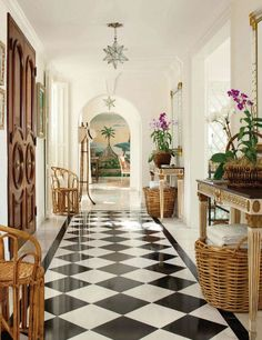 Longitudinal foyer in Lyford Cay by Andrew Racquet. Black and white floors, Moravian star pendants, matching console tables, bent bamboo midcentury chairs, doors with centered gold knobs, tropical mural on the far wall and pale turquoise and white lattice room to the right - definition faaaaabulous.