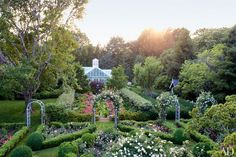 'New Dawn' climbing roses are trained over arches; a Lalanne Minotaur statue stands in front of the greenhouse.