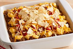 This Cheesy Pasta Nacho Bake is hearty with salsa, sour cream and ground beef—all covered with a topping of cheesy crushed tortilla chips. Tortillas, Baked Nachos, Cheese Stuffed Shells, Taco Bake, Enchilada Bake, Kraft Recipes, Casserole Recipes, Taco Casserole, Cornbread Casserole
