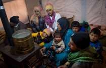 Members of a Syrian refugee family huddle around a stove inside their shelter days ago in Lebanon's Bekaa Valley.