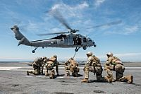 """151017-N-WO404-130  PACIFIC OCEAN (Oct. 17, 2015) Sailors assigned to Explosive Ordnance Disposal Mobile Unit (EODMU) 3, Platoon 3-1-1 and Chilean navy sailors brace themselves after fast-roping out of an MH-60S Seahawk helicopter, assigned to the """"Black Knights"""" of Helicopter Sea Combat Squadron (HSC) 4, during a fast-roping exercise on the flight deck of aircraft carrier USS George Washington (CVN 73). UNITAS 2015, the U.S. Navy's longest running annual multinational maritime exercise, is…"""