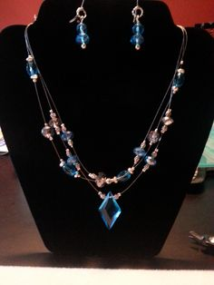 This is a nice multi-strand illusion necklace with royal blue glass beads and a beautiful diamond-shaped center focal piece on one strand.