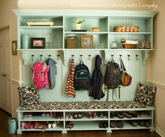 Mudroom wall that has space for shoes, bench for sitting, hooks for coats and backpacks and storage above.