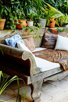 Wood engraved daybed with a mix of patterned pillows surrounded by potted plants.