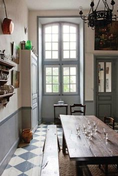 31 Beautiful French Farmhouse Style Moments {Decor Inspiration} - Hello Lovely French farmhouse kitchen with blue grey palette, farmhouse table, checked floor, tall windows, and copper pots.