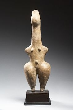 Amlash - steatopygous idol  Statuette of a stylized female figure with outstretched stumpy arms, elongated neck, globular head and high hair ornament.  Terracotta.  Northwestern Iran, Marlik culture, early 1st millenium B.C.  Height : 17 cm