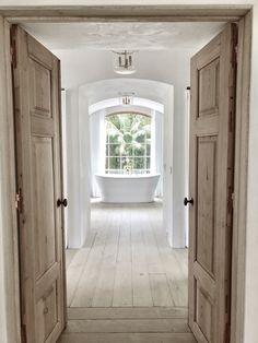 Vintage doors to master bathroom of Malibu Mediterranean Modern Farmhouse - Giannetti Home and Jones Builders Group