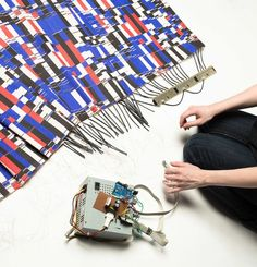 The standard fibres were interwoven with thin nichrome wires which are driven by four 24V industrial DC power supplies. When the power supplies are turned on, the wires quickly heat-up and the thermochromatic dyes react to change the colour of the patterned fabric  http://www.plusplasticelectronics.com/SmartFabricsTextiles/electronic-colour-changing-fabric-demonstrated-112393.aspx http://vimeo.com/91989013