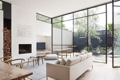 "The designers explain, ""These steel windows played an integral part in making the interior feel larger and more open by blurring the boundaries between the interior and exterior."" A grey Halcyon Lake area rug, an oak chair from MAP, and Hans Wenger Wishbone chairs make for a simple, neutral palette. The painting over the fireplace is by Kate Hendry."