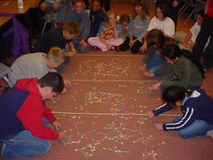 Students cluster around a carpeted area strewn with molecules made from toothpicks and gumdrops. Ozone game.