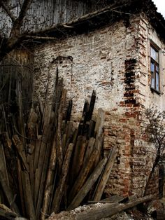 old brick building... woodpile ... photographer unknown #stone