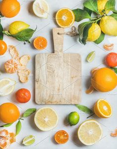 #Variety of fresh citrus fruit  Variety of fresh citrus fruit for making juice or smoothie and wooden chopping board in center over light grey marble background top view copy space. Healthy eating vitamin clean eating concept