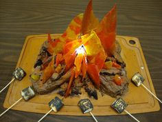 This cake was made for my sons cub scout troop.  I melted red, yellow, and orange jolly ranchers on a cookie sheet. After they cooled, I broke the candy apart to make the flames. There is a battery-powered flashlight in the middle.  The toasted marshmallows were my sons idea!