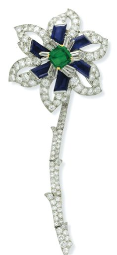 A DIAMOND, EMERALD AND SAPPHIRE FLOWER BROOCH, BY CARTIER Designed as a flower blossom, with a square-cut emerald pistil, enhanced by baguette-cut diamonds and calibré-cut sapphires, to the openwork circular-cut diamond petals and articulated circular-cut diamond stem, mounted in platinum and 18k gold, with French assay marks and maker's mark