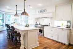Gorgeous open kitchen design. Hardwood floors, white cabinets, light countertops, brass pendants and hardware