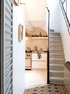 Cocina minimalista con pisos de calcáreos y escalera de hormigón en el ph reciclado de una artista y un director de cine jóvenes.