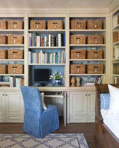Birou incorporat in biblioteca. Decor cu cutii depozitare pe rafturi. Diverse modele de tapet (forme goemetrice cu motive china) combinate pe tablia din spate a bibliotecii.  Albastru ca pata de culoare intr-un decor combinatie de pardoseala maro inchis cu mobila alb/crem. Decor clasic