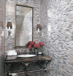 The tiles in this powder room reflect both artificial and natural light and can make the space appear bigger than it really is.