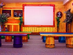 Screen is made out of white sheet and put a styrofoam frame around it. (cheap way to make a screen for youth area? obviously without kid decor) Benches are made out of buckets and doors. Then painted everything bright. Kids Church Decor, Kids Church Rooms, Sunday School Decorations, Church Nursery, Kids Decor, Children Church, Church Ideas, Sunday School Rooms, Preschool Rooms