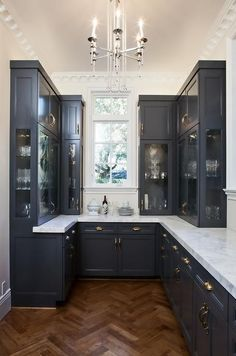 Absolutely stunning butler's pantry features navy blue cabinets adorned with brass hardware topped with thick gray and white marble countertops.