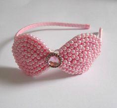 Tiara forrada de fita de cetim com um laço bordado de contas plásticas de pérola rosa (as contas são costuradas individualmente, não coladas).