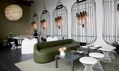 Home Delicate Restaurant Milan, Italy Logica: Architettura  The different zones of this restaurant blend the inside with the outside with garden-party-esque details like delicately woven chairs, lush walls of greenery and flowers, and birdcage motifs on the walls.