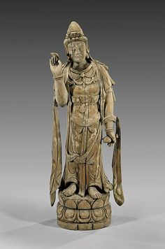 """TALL ANTIQUE CARVED WOOD GUANYIN Tall and antique, Chinese carved and polychrome wood figure; of Guanyin, standing in draped robes, holding her vase of tears and foliage in the other hand, atop a double lotus vase, probably 18th Century; H: 49 1/2"""""""