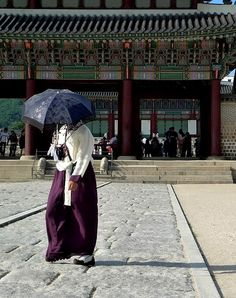 A young woman in traditional Korean dress walks through the expansive grounds of the Gyeongbokung Palaces in Seoul. These palaces, first constructed in 1394, are the largest in Seoul, and beautiful to wander as well as being awe-inspiring in size.