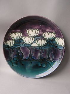Earthenware charger, decorated with a design of water-lilies and leaves in a pond, the raised slip-trailed outlines in dark green, filled in with coloured lead glazes: white for the lilies and blue-green for the leaves on a purple background.