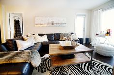 white walls, black leather sectional, industrial coffee table | Style At Home: Monika Hibbs Of The Doctor's Closet