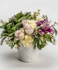 Lavender Mist This luxury collection of purple calla lilies, lavender roses and white hydrangea with unique and textural accents is designed in a white ceramic container for this simple yet stunning design.