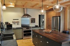 Farmhouse modern kitchen. wood ceiling, soapstone counter, reclaimed wood island