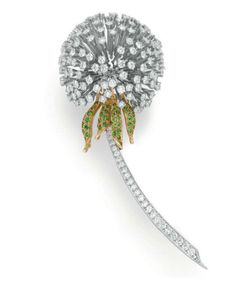 A DIAMOND AND TSAVORITE GARNET DANDELION BROOCH, BY TIFFANY & CO. Designed as a dandelion flower, with articulated circular-cut diamond seeds, to the circular-cut tsavorite garnet leaves and graduated circular-cut diamond stem, mounted in platinum and 18k gold Signed Tiffany & Co.