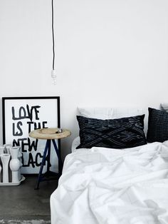white bedding + patterned pillows + white walls + exposed bulb + love is the new black + stool