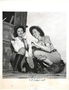 """Wash Day in the Far East Two U.S. Army Nurses, Mildred Clemson (left) and Mary Louise Harrison (right), do their washing in a bucket """"somewhere in the Far East."""" Note the boots worn by the girls - necessary equipment during the rainy season in India, where many American nurses are stationed. 1943 ~"""