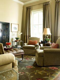 Tall draperies to match the high ceilings create drama in this elegant living area. A floral rug adds color and vitality, accentuating the solid-colored elements found throughout the room. A rustic media cabinet at texture and interest to the space while keeping the television hidden from view.