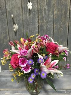 Stargazer lilies accented with roses, alstromeria, waxflower, asters, and tropical foliage.