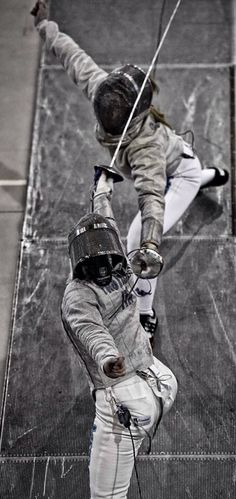 Overhead action shot of women's sabre - left-handed vs. right-handed fencers.