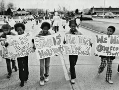 Description of  APR 4 1981 - Children, carrying signs calling for the birthday of slain civil rights leader Martin Luther King Jr. to be named a national holiday, march in a parade Saturday commemorating the 13th anniversary of his assassination. The parade, with about 150 marchers, proceeded west on Martin Luther King Boulevard (32nd Avenue) from Monaco Parkway to York Street, then south to the statue of King in City Park. (Dave Buresh/The Denver Post)