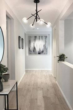 A wide entry all the way. Love the contrast of the light flooring and black accents in this gorgeous home of Builder: modern hallway Hallway Inspiration, Home Decor Inspiration, Hallway Decorating, Interior Decorating, Hallway Designs, Hallway Ideas, Entry Hallway, Lights For Hallway, Hallway Lamp