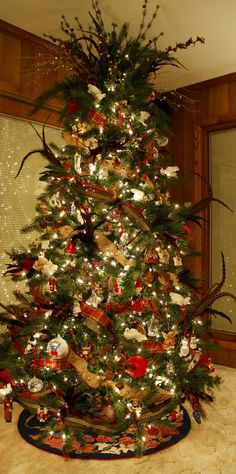 Beautiful traditional Christmas tree with birds, feathers and burlap ribbons